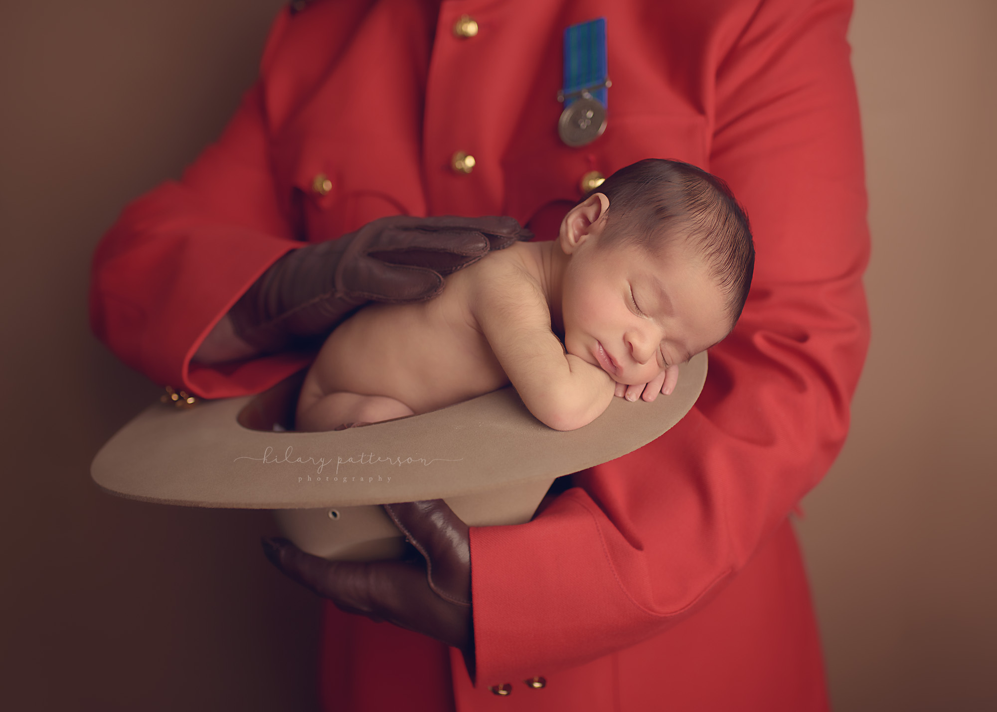 newborn-boy-photographer-fraser-valley-vancouver-hope-chilliwack-red-serge-police-pose-prop-kamloops